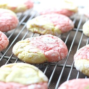a fresh batch of pink and yellow Strawberry Lemonade Cookies topped with powdered sugar cooling on rack