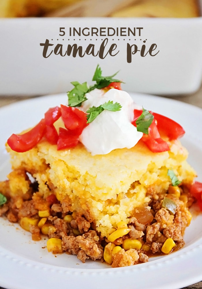 a close up of a piece of tamale pie made with cornbread and cheese and topped with tomatoes and sour cream on a white plate. A casserole pan with filled with tamale pie that has a square cut out with a wooden spoon in it's place. The words five ingredient tamale pie is written at the top of the image.