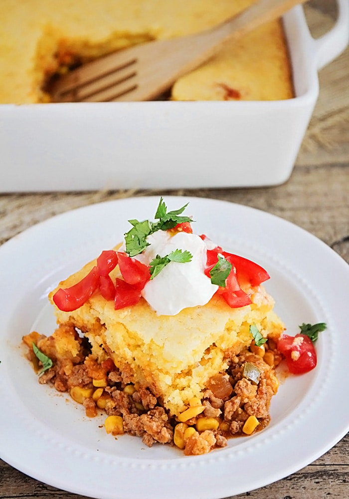 a square of tamale pie made with cornbread and cheese and topped with tomatoes and sour cream on a white plate. A casserole pan with filled with tamale pie that has a square cut out with a wooden spoon in it's place.