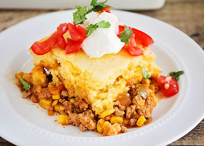 a serving of this easy tamale pie recipe with cornbread and cheese and topped with tomatoes and sour cream on a white plate