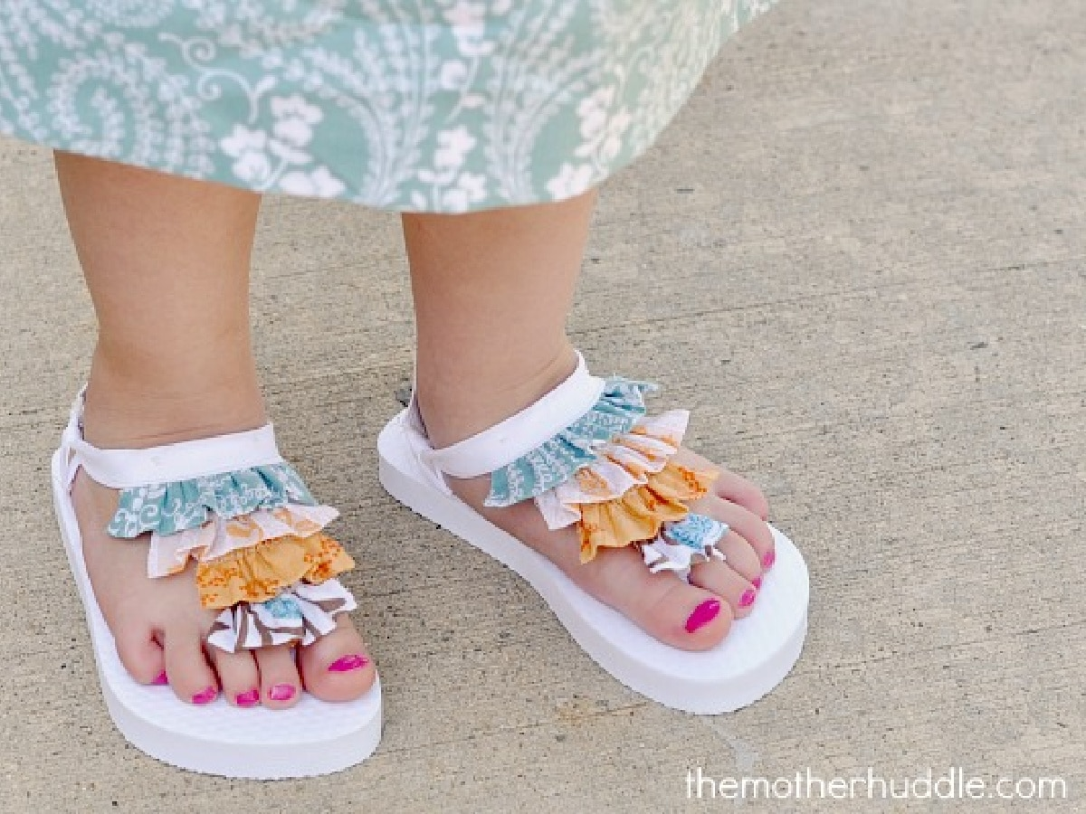 little feet wearing white flip flops with colorful ruffles