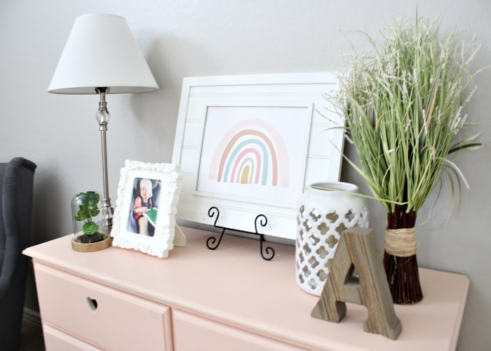a pink dresser with pictures, a lamp, a plant and a wooden letter A on top