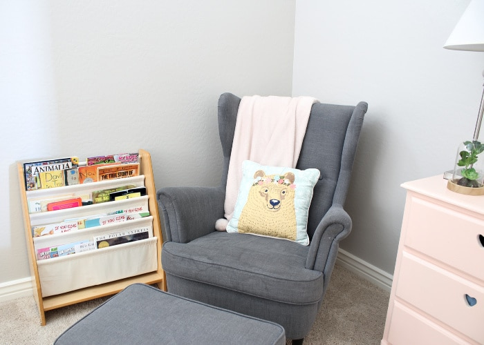 a gray chair with a matching ottoman in the corner of a room next to a small book shelf and a pink dresser