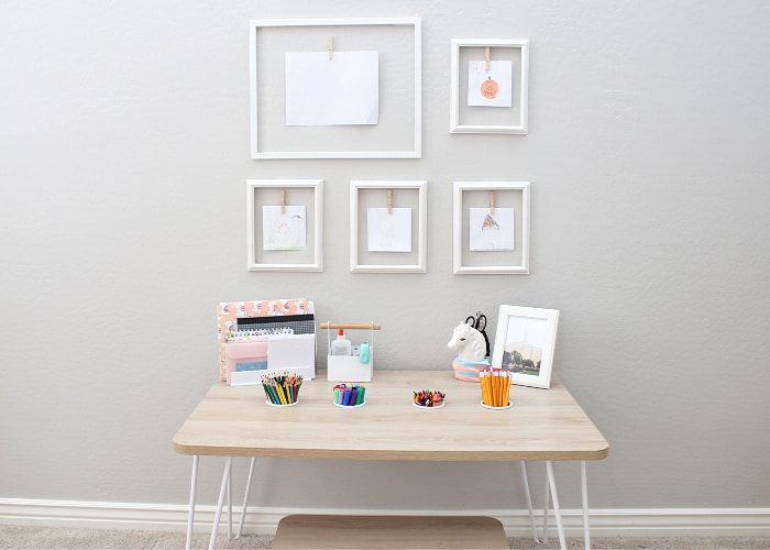 a wooden art table against a wall with picture frames hanging in front of it on the wall