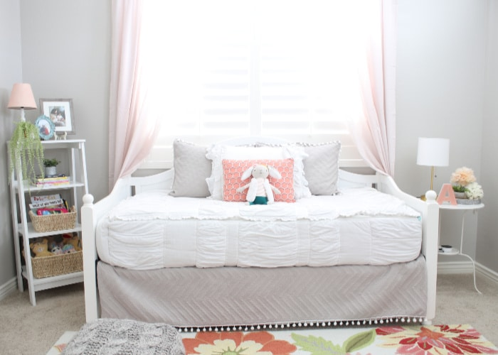 a little girl's bed with several pillows and a stuffed bunny on the bed