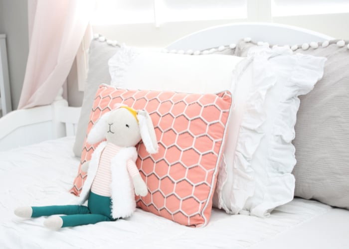 a stuffed rabbit in front of pillows sitting on a bed