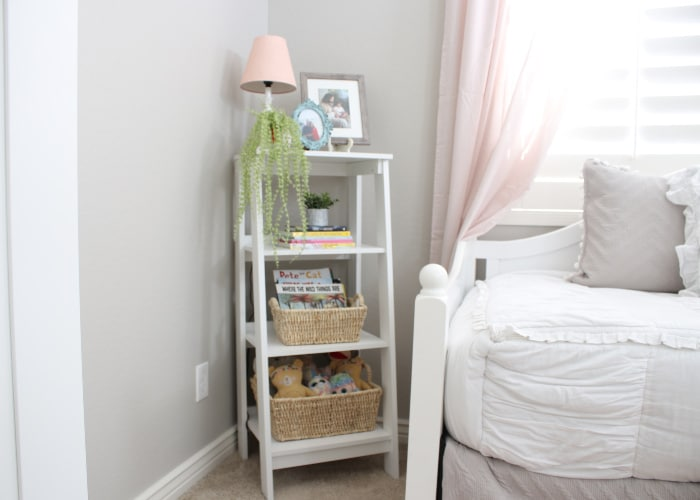 a shelf in a younger girl's bedroom with pictures and baskets on the shelves
