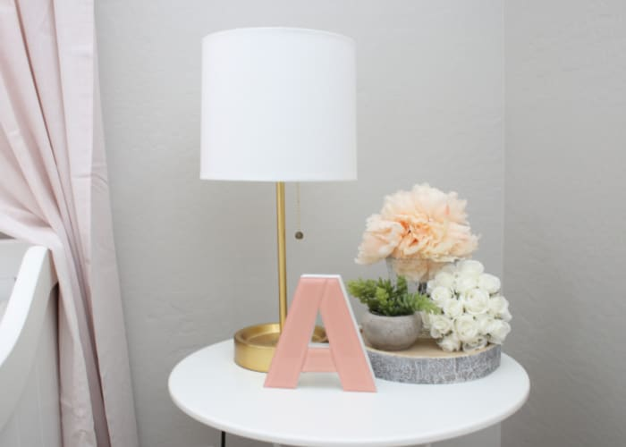 a white circular table with a lamp and a pink letter A on top
