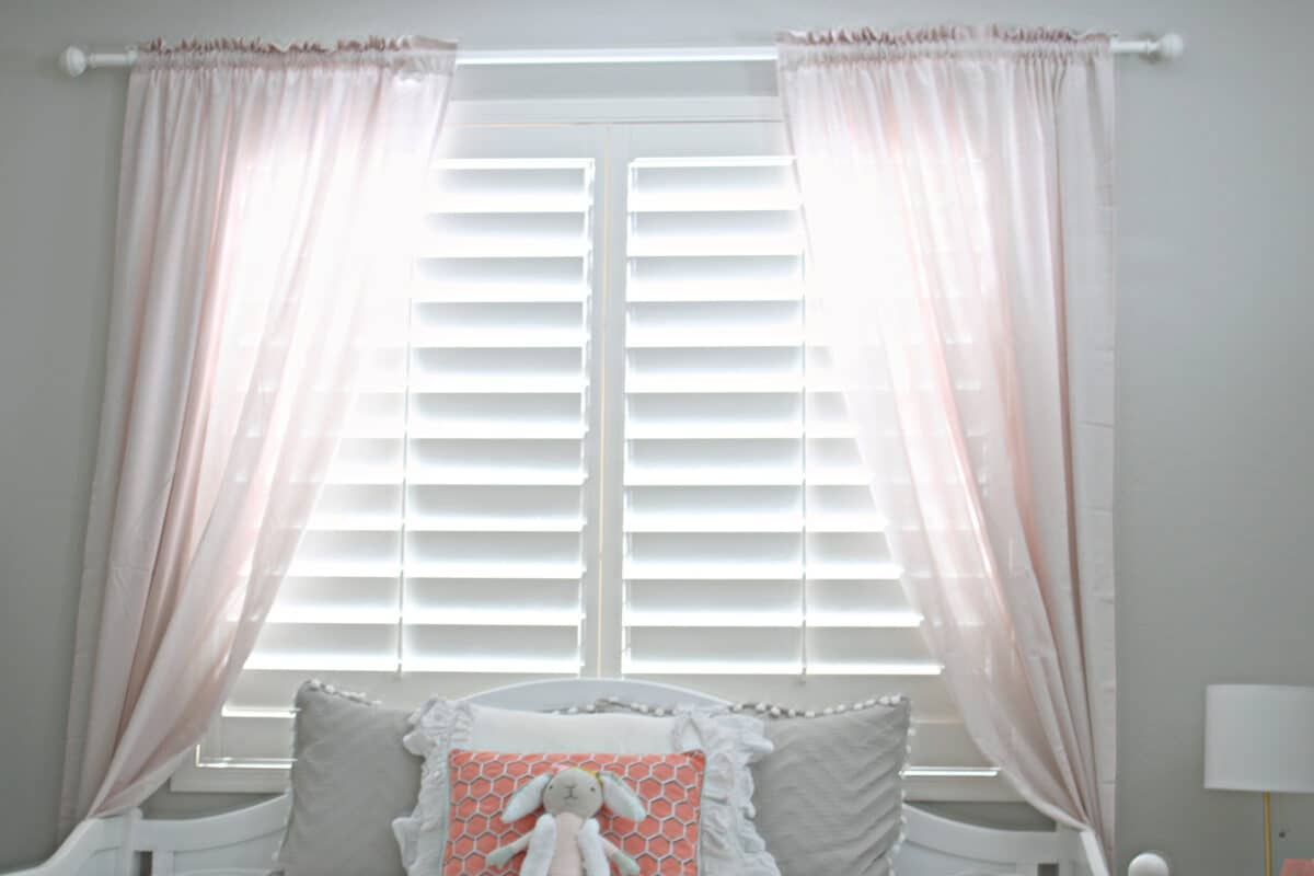 pink curtains hanging in front of a window covered by white shutters