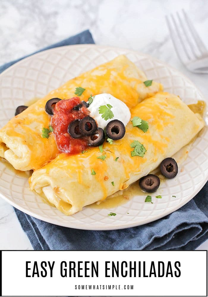 a white plate with two Green chili Enchiladas topped with salsa, olives, cheese, sour cream and parsley made using this easy recipe