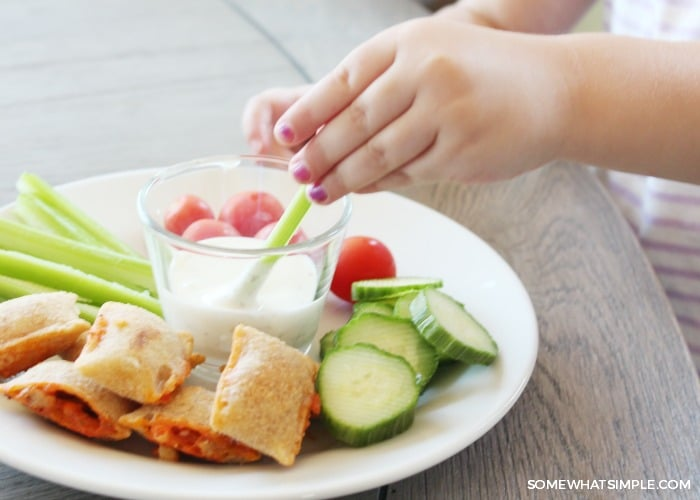 a child's hand dipping a celery stick into a dish of ranch on a plate with other vegetables and pizza bites