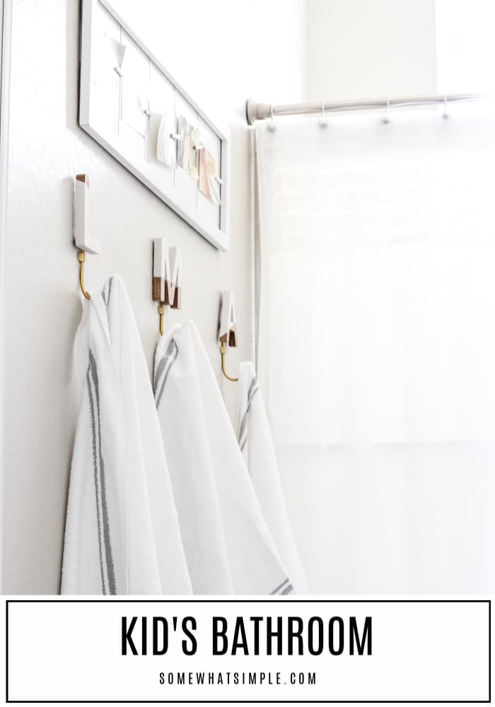 monogram towel racks hanging in a child's bathroom below a picture board holding up pictures with clothespins