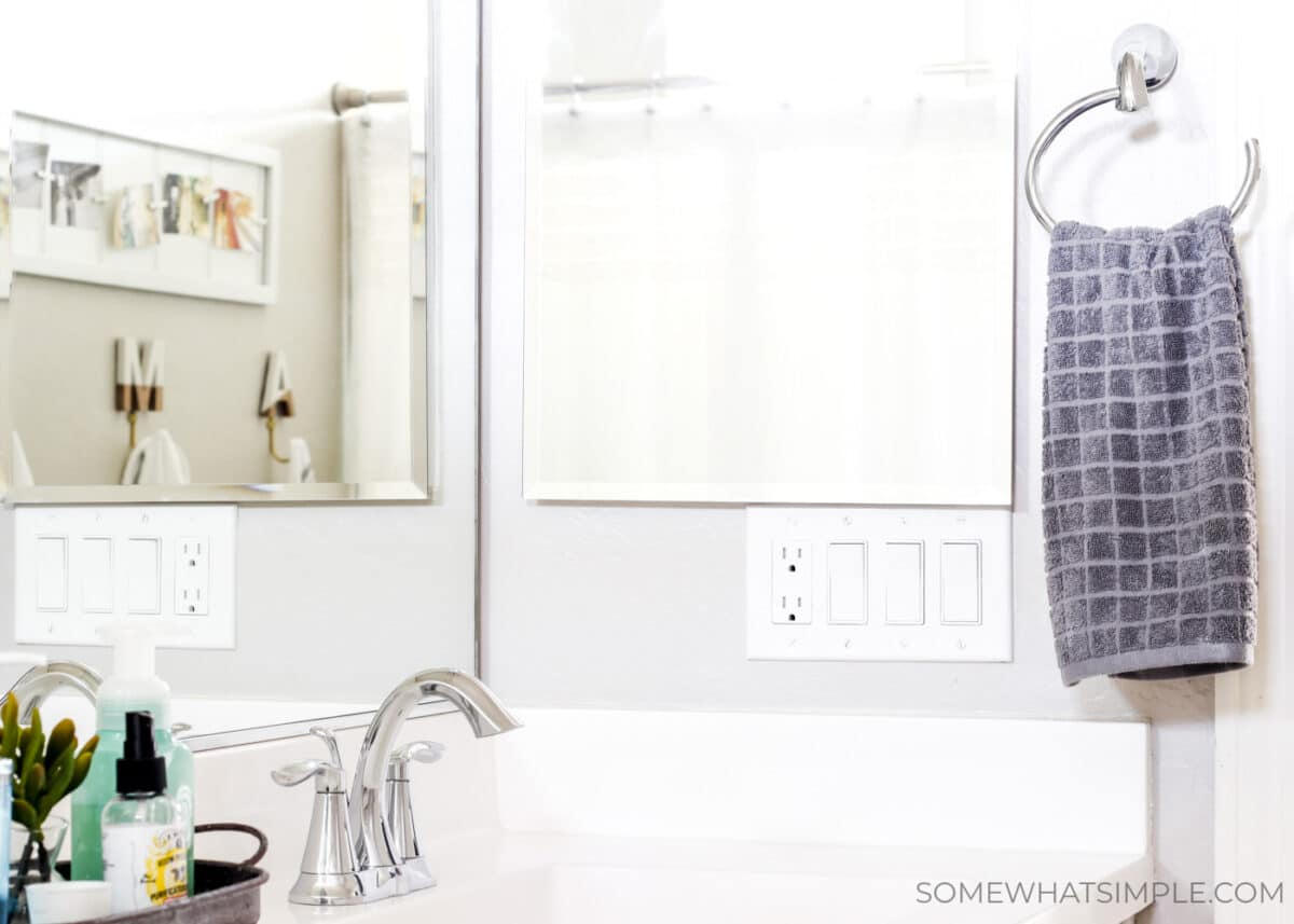 a gray hand towel hanging from a towel rack next to a mirror in bathroom