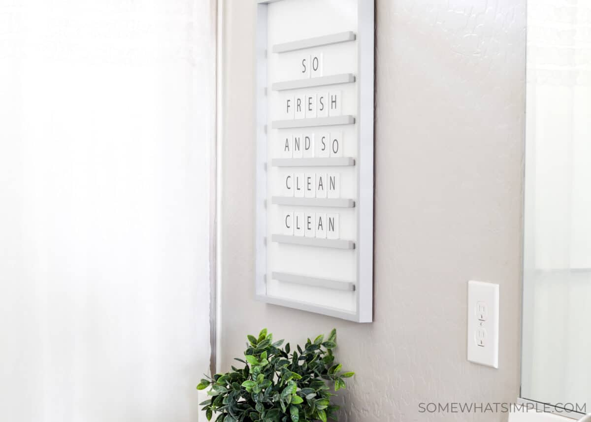 a letter board hanging on the wall above a toilet that reads, so fresh and so clean clean