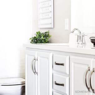a kids bathroom that has white cabinets with nickle hardware