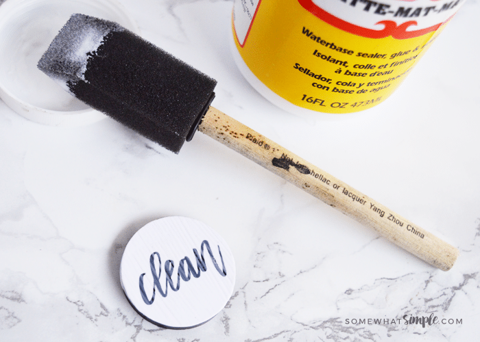 a foam brush has just painted mod podge over a circular magnet with the clean dishwasher free printable