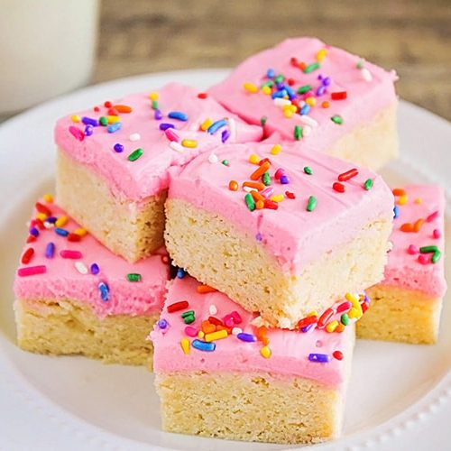 a plate of old fashioned sugar cookies topped with pink frosting and colorful sprinkles