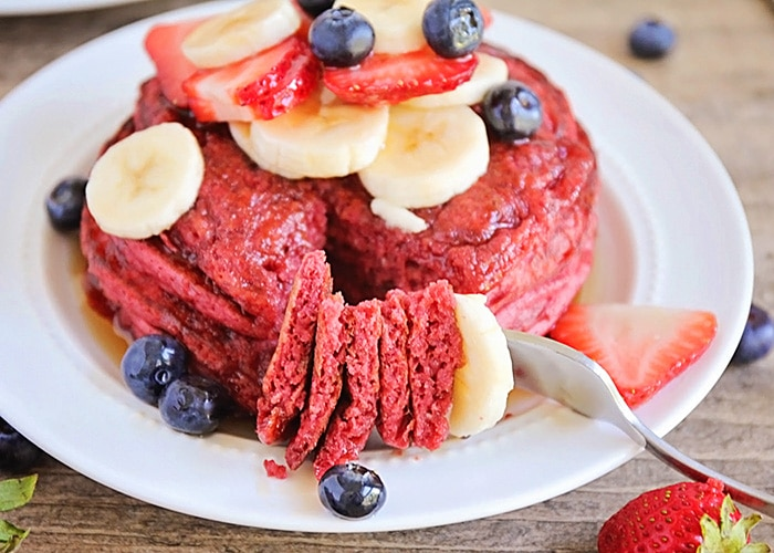 a plate full of Red Velvet Pancakes made with this easy Recipe and topped with bananas strawberries and blueberries