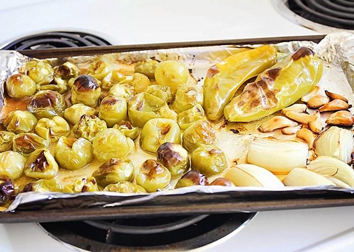 roasted tomatillos, garlic and onions on a baking sheet