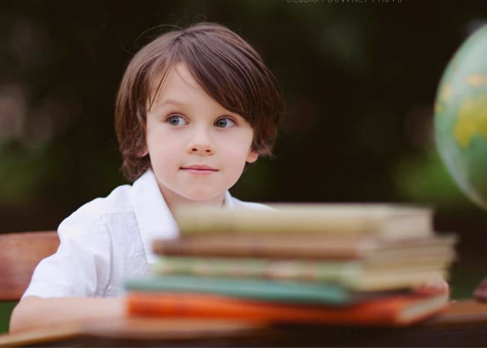 a little boy sitting at a desk with a stack of books on the desk