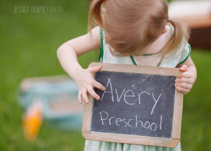 a little girl holding a chalkboard that says Avery preschool