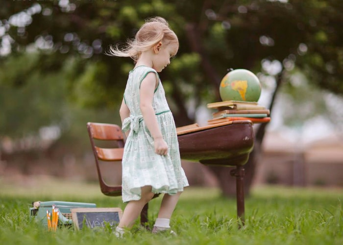 a little girl walking by a vintage school desk that is outside