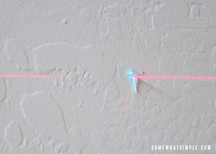a nail in a wall with a laser level line across it
