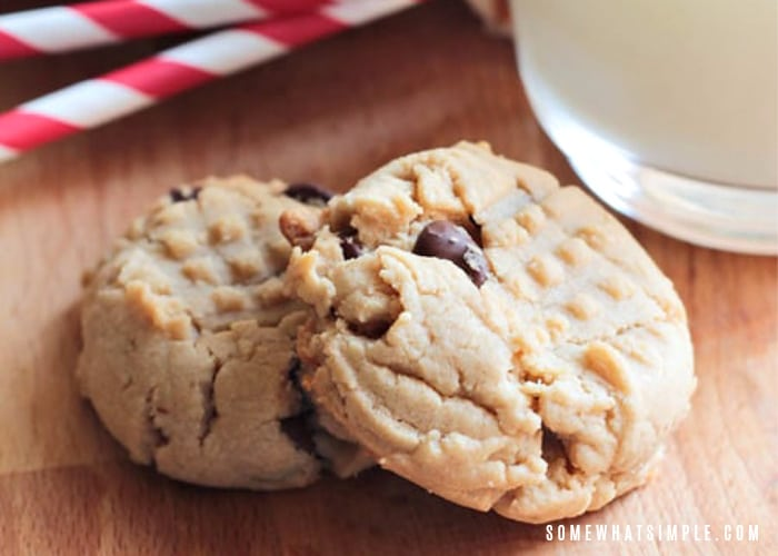 two peanut butter chocolate chip cookies laying on top of each other on a wooden table