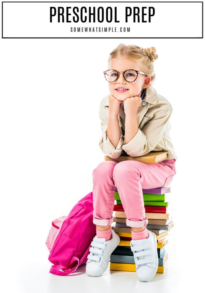 little girl sitting on a stack of books with backpack preparing for preschool