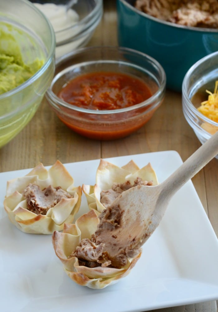 wonton cups being filled with refried beans