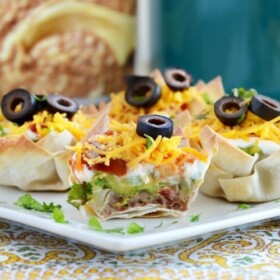 seven layer dip cups on a plate