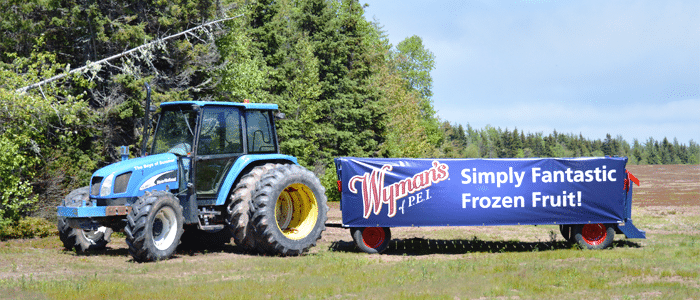 a tractor pulling a trailer with a Wyman's of Maine sign