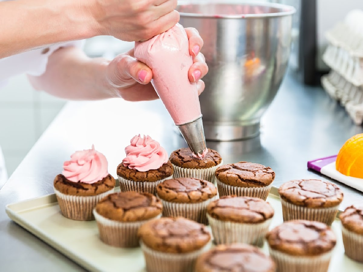 cupcake baking tips with woman frosting chocolate cupcakes with pink frosting