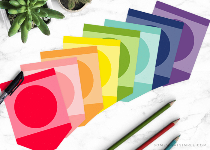 crayon printables in every color of the rainbow laid out on a counter