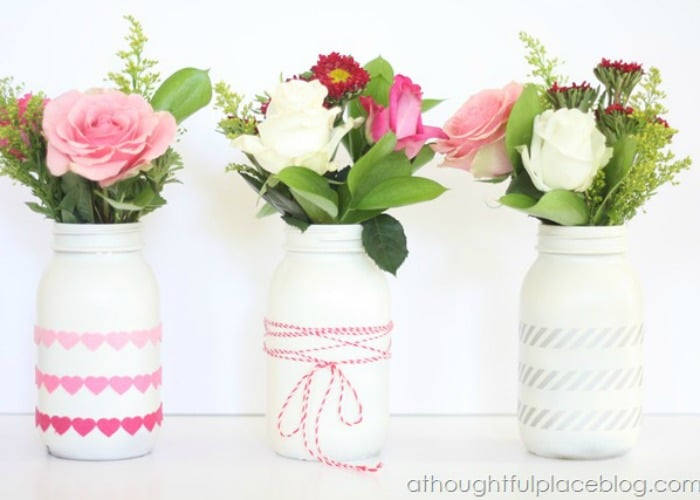 jars painted white with flowers inside that are being used as a vase