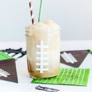 a mason jar painted to look like a football with a foaming drink inside