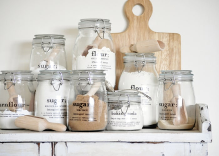 Mason Jar filled with baking ingredients on a shelf with labels on them are a cute farmhouse Decor idea