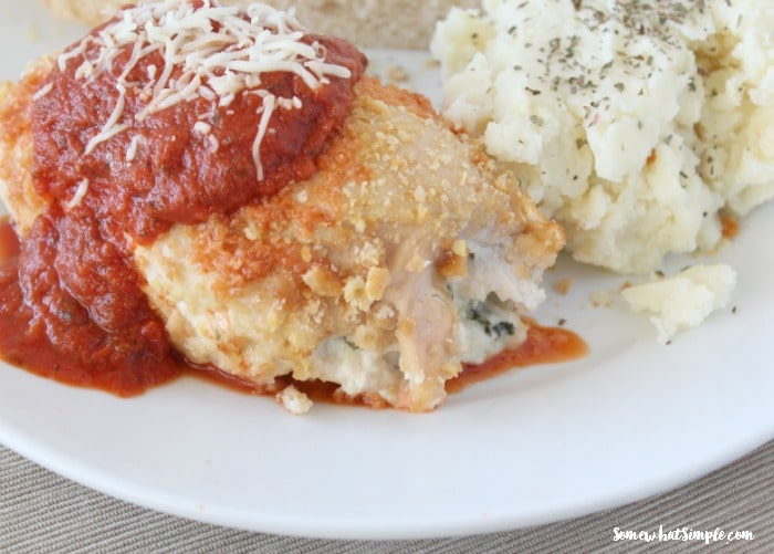a piece of stuffed chicken parmesan topped with marinera sauce and cheese with a side of mashed potatoes on a white plate