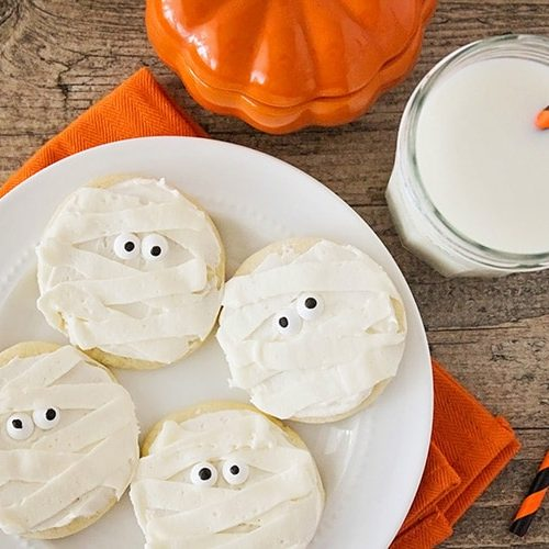 Halloween Mummy sugar Cookies on a plate next to a glass of milk