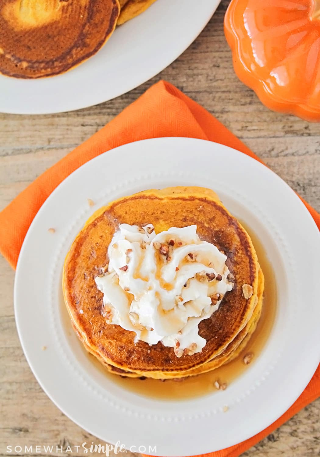 easy fluffy Pumpkin Pancakes Recipe on a white plate topped with whipped cream on a white plate sitting on top of an orange napkin