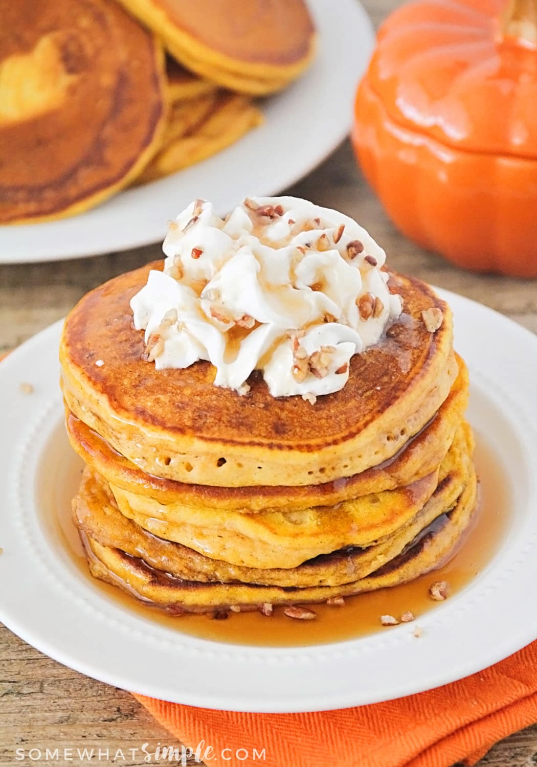 Recipe for Easy Pumpkin Pancakes on a white plate topped with whipped cream