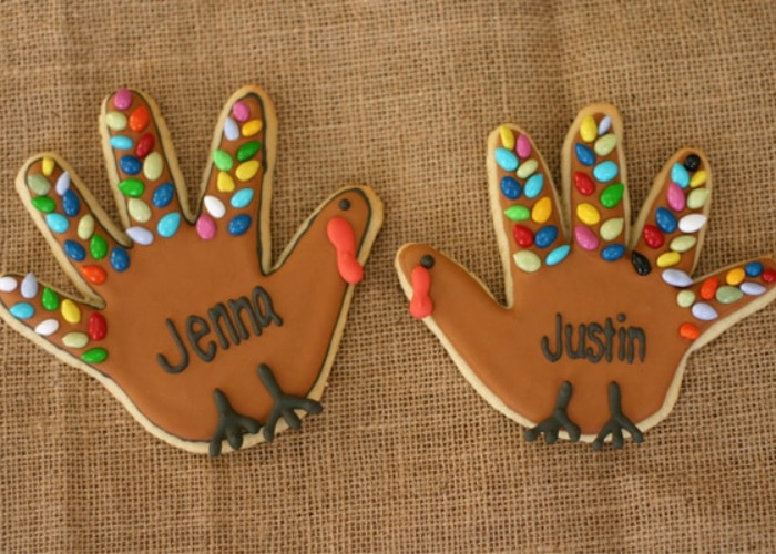 two handprint turkey cookies with brightly colored decorations