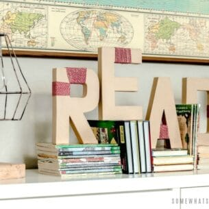 yarn wrapped letters on a book shelf that spell out the word read