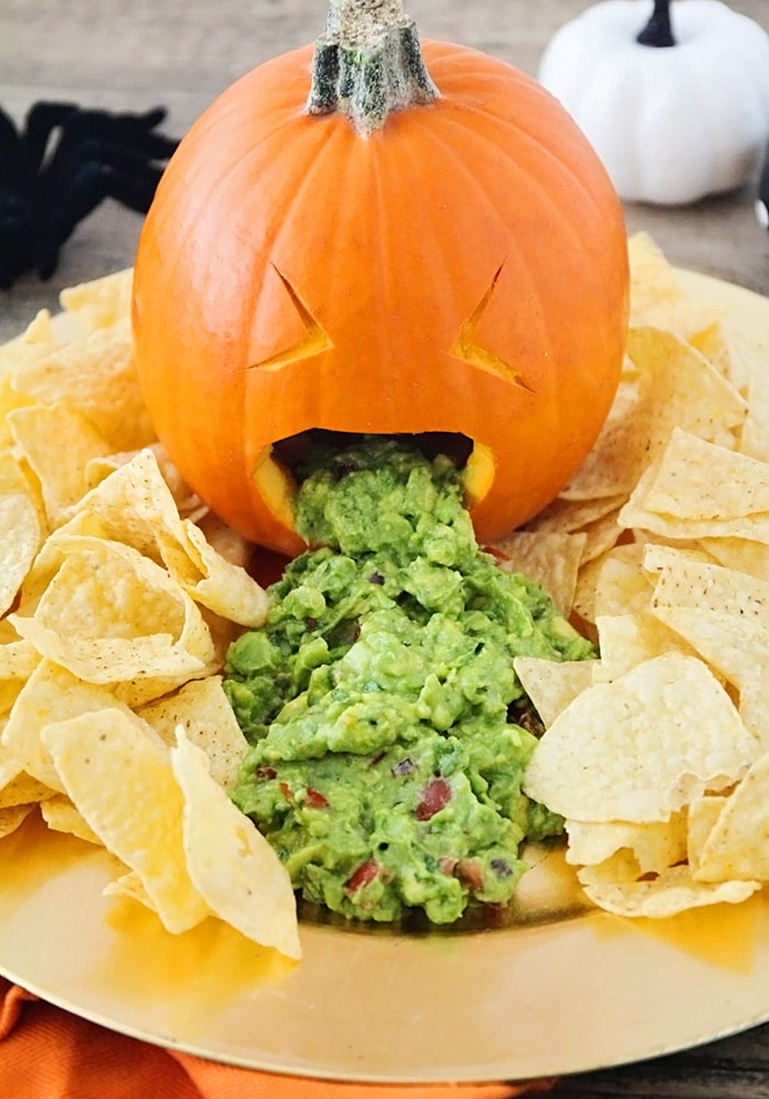 a pumpkin puking out guacamole on a serving platter with chips