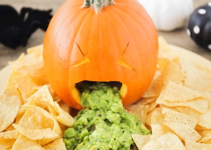 a barfing pumpkin with guacamole coming out of it's mouth with tortilla chips spread all around