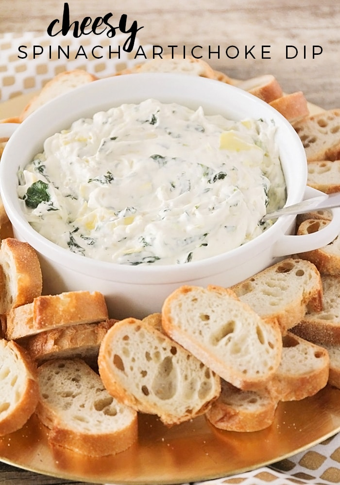 bowl Spinach Dip made from this easy recipe recipe in a white bowl with slices of bread around it. At the top of the image, the words cheese spinach artichoke dip are written in black letters.