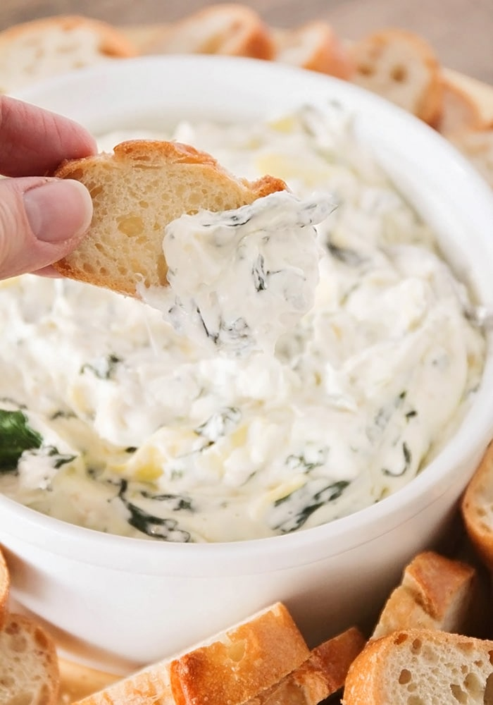 a hand dipping a piece of bread into a hot bowl of spinach artichoke dip
