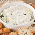 a white bowl filled with Cheesy Spinach Artichoke Dip that has a spoon stuck in the dip. Surrounding the bowl are slices of baguettes.