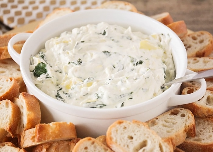 Cheesy Spinach Artichoke Dip in a serving bowl with bread slices around it makes a simple super bowl snack