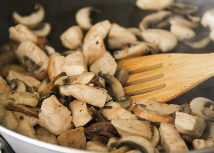 a wooden spoon stirring pieces of chicken and mushrooms in a skillet
